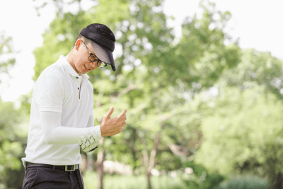 A golfer holds his wrist. Having wrist pain after golf could be caused by a number of conditions.