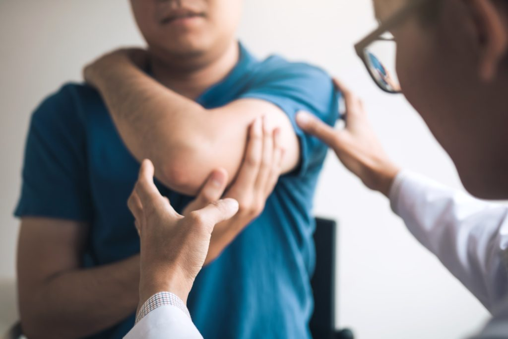 doctor treating fractured elbow